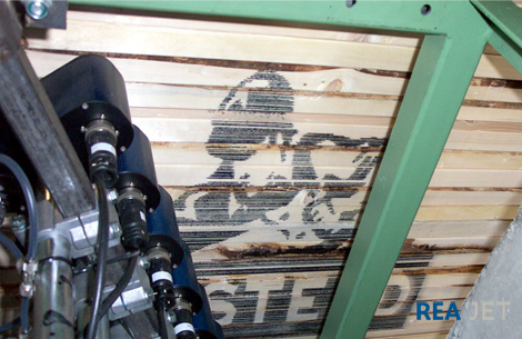 Foto: 32-nozzles Large Character printing system - The side of a wood stack marked with a 700x1200 mm high logo